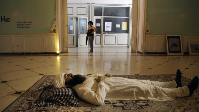 "Havana : A woman stops to look at the realistic sculpture of the late al-Qaeda leader Osama bin Laden by artists Alberto Lorente, Manolo Castro and Julio Lorente titled ""He"" that is on display at the Superior Institute of Arts during the 11th Havana Biennial contemporary art exhibition in Havana, Cuba, Thursday, May 10, 2012. AP/PTI(AP5_11_2012_000017A)"