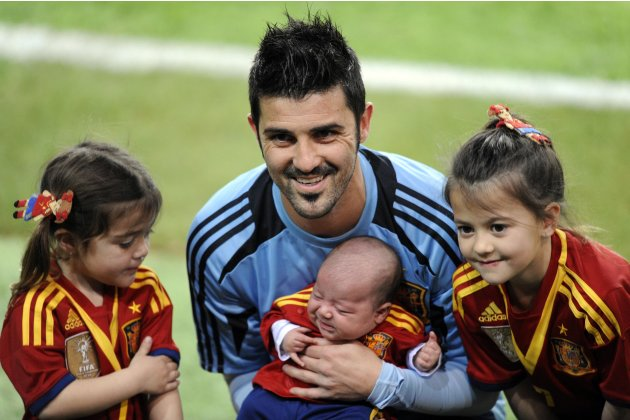 Spain's player David Villa poses with his children after a training session at El Molinon stadium in Gijon