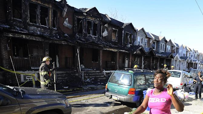 A woman cries as she walks past Philadelphia firefighters working on burned row homes on Saturday, July 5, 2014, in Philadelphia. A fast-moving fire in southwest Philadelphia early Saturday left four children dead and burned through a number of adjoining homes. (AP Photo/Michael Perez)