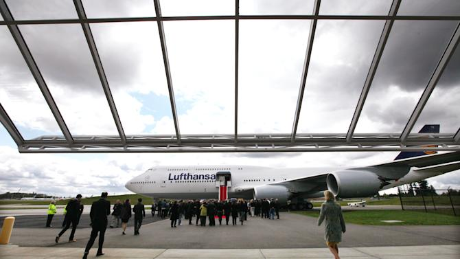 Guests walk toward the first Boeing 747-8 Intercontinental launch jet on the tarmac following remarks inside during a delivery ceremony Tuesday, May 1, 2012, in Everett, Wash. Lufthansa is the launch customer for the Intercontinental and will start service with the airplane between Frankfurt, Germany and Washington, D.C. The 747-8 Intercontinental is a stretched, updated version of the iconic 747 and is expected to bring double-digit improvements in fuel burn and emissions over its predecessor, the 747-400, and generate 30 percent less noise. Boeing delivered the first 747-8 Intercontinental to a private customer in February, more than a year after originally planned. (AP Photo/Elaine Thompson)