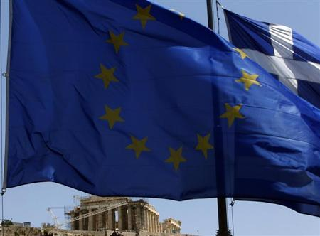 A E.U. flag and a Greek flag flutter in front of the monument of Parthenon on Acropolis hill in Athen