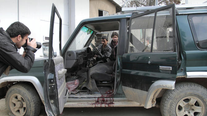 An Afghan intelligence officer, center, tries to turn on a vehicle used by an insurgent, who was killed by security forces,  in Kabul, Afghanistan, Sunday, Feb. 24, 2013. A series of early morning attacks hit eastern Afghanistan Sunday, with three separate suicide bombings in outlying provinces and a shootout between security forces and a would-be attacker in the capital city of Kabul.   (AP Photo/Musadeq Sadeq)