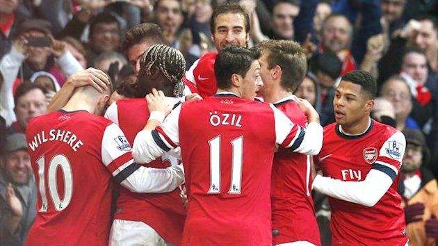 Arsenal players mob Santi Cazorla (obscured) after his first goal against Fulham (Reuters)
