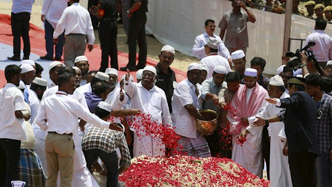 People throw rose petals on the grave of former Indian President A.P.J. Abdul Kalam during his funeral ceremony in Rameswaram