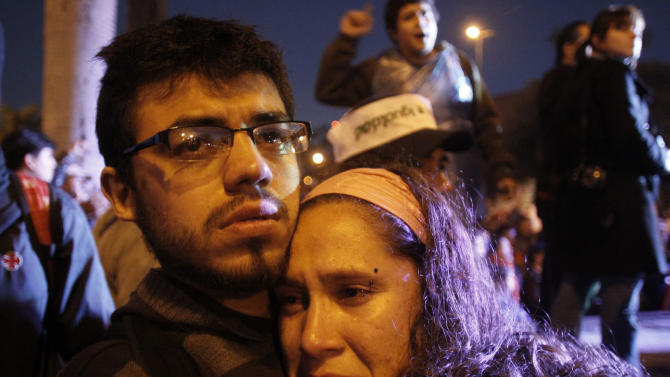 Supporters of Paraguay's President Fernando Lugo embrace outside Congress after the Senate voted to remove Lugo from office in Asuncion, Paraguay, Friday, June 22, 2012. Paraguay's Senate removed Lugo from office in a rapid impeachment trial on Friday, and the leftist former priest said he was stepping aside even though he considered his ouster a blow to democracy. (AP Photo/Cesar Olmedo)