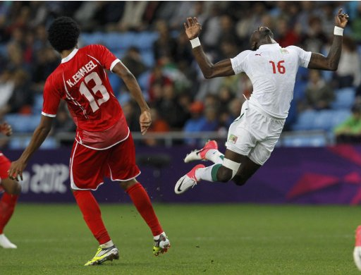 Senegal's Pape Souare falls next to UAE's Khamis Esmaeel during their men's Group A football match at the London 2012 Olympic Games