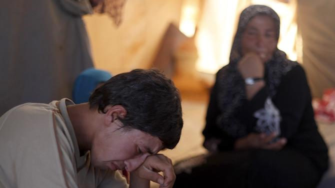 In this Tuesday, Sept. 11, 2012 photo, Basel Baradan, an 18-year-old farmer who fled his southern restive border town of Daraa, Syria with his family in July, wipes his eyes as he speaks during an interview at the Zaatari Refugee Camp, in Mafraq, Jordan. Jordan now hosts 200,000 Syrians, the largest number of refugees of any neighboring country. After months of delay, Jordan finally opened its first official refugee camp in July at Zaatari, near the border with Syria.(AP Photo/Mohammad Hannon)