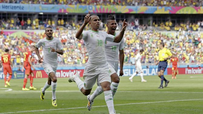 Algeria's Sofiane Feghouli, centre, celebrates after scoring the opening goal during the group H World Cup soccer match between Belgium and Algeria at the Mineirao Stadium in Belo Horizonte, Brazil, Tuesday, June 17, 2014. (AP Photo/Hassan Ammar)
