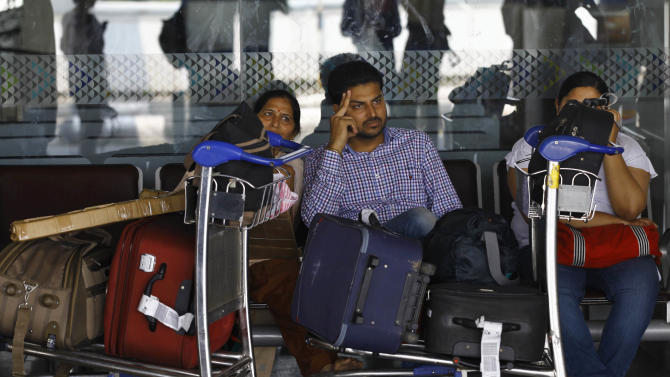 Passengers wait outside the Kingfisher Airlines reservation counter after their flight was canceled at the domestic airport in Mumbai, India, Monday, Oct. 1, 2012. Kingfisher says it has canceled several flights Monday due to a labor dispute with its workforce, local media reported. (AP Photo/Rafiq Maqbool)