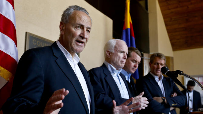 Sen. Chuck Schumer, D-N.Y., left, speaks to the media as, from second left, Sen. John McCain, R-Ariz., Sen. Michael Bennett, D-Colo., and Sen. Jeff Flake, R-Ariz., listen in during a news conference after their tour of the Mexico border with the United States on Wednesday, March 27, 2013, in Nogales, Ariz.   The senators are part of a larger group of legislators shaping and negotiating details of an immigration reform package vowed Wednesday to make the legislation public when Congress reconvenes next month. (AP Photo/Ross D. Franklin)
