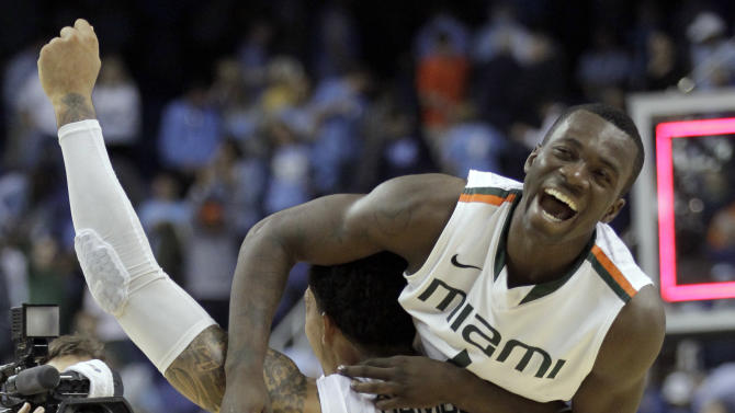 Miami's Durand Scott, top, is lifted by Julian Gamble, bottom, after an NCAA college basketball game against North Carolina in the championship of the Atlantic Coast Conference tournament in Greensboro, N.C., Sunday, March 17, 2013. Miami won 87-77. (AP Photo/Bob Leverone)