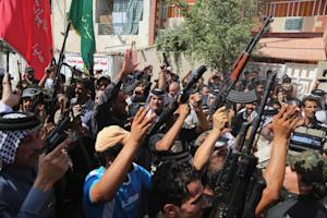 Iraqi Shiite tribal fighters raise their weapons and…