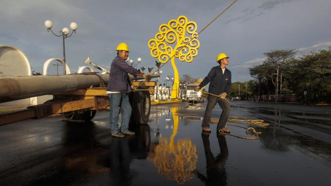 Workers place metal trees on Bolivar Avenue in Managua