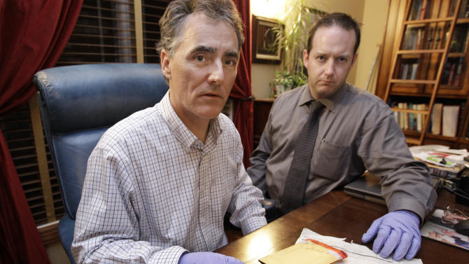 In this photo taken Friday, Nov. 30, 2012, in Chicago, Cook County Sheriff Tom Dart, left, and sheriff's detective Jason Moran are photographed with three recently discovered vials of mass murderer John Wayne Gacy's blood. The sheriff's office is creating DNA profiles from the blood of Gacy and other executed killers and putting them in a national DNA database of profiles created from blood, semen, or strands of hair found at crime scenes and on the bodies of victims. What they hope to find is evidence that links the long-dead killers to the coldest of cold cases and prompt authorities in other states to submit the DNA of their own executed inmates and maybe evidence from decades-old crime scenes to help them solve their own cases. (AP Photo/M. Spencer Green)