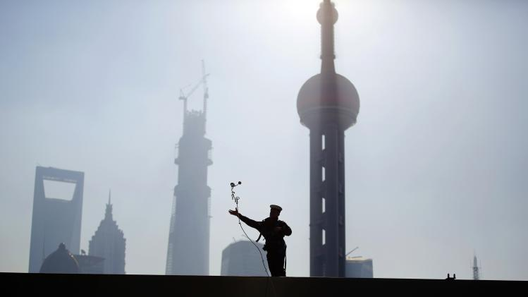 A sailor from British Royal Navy destroyer HMS Daring tries to catch a mooring line to dock in the north side of the bund at Huangpu River in Shanghai