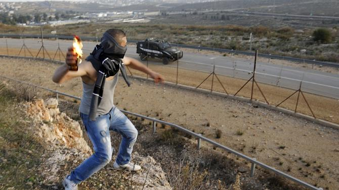 Palestinian protester throws a Molotov cocktail towards Israeli border police jeep during clashes near Israel's Ofer Prison near the occupied West Bank city of Ramallah