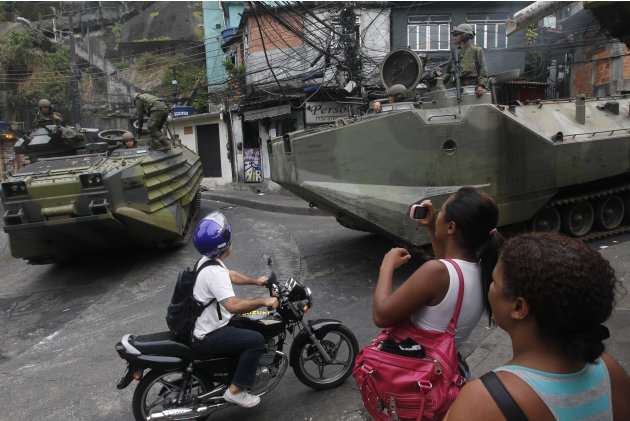 Residents are seen next to armored cars after the police invaded the Rocinha slum, in Rio de Janeiro, Sunday, Nov.13, 2011. Elite police units backed by armored military vehicles and helicopters invad
