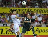 Real Madrid&#39;s Cristiano Ronaldo (R) fights for the ball with Sevilla&#39;s Emir Spahic during a Spanish league football match at the Sanchez Pizjuan stadium in Sevilla. Sevilla won 1-0