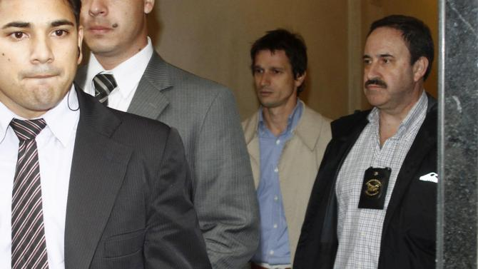 Lagomarsino leaves a news conference escorted by plainclothes Gendarmerie officers in Buenos Aires