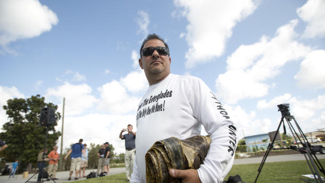 "Trapper ""Python Dave"" Leibman holds a roll of snake skins he is selling at the Python Challenge kick-off in Davie, Fla. Saturday, Jan. 12, 2013. Roughly 2,050 pythons have been harvested in Florida since 2000, according to the conservation commission. It's unknown exactly how many are slithering through the wetlands. (AP Photo/J Pat Carter)"