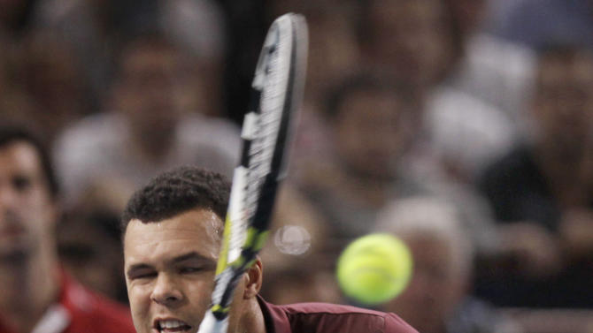 France's Jo-Wilfried Tsonga returns the ball to Switzerland's Roger Federer, during their final match of the Tennis Masters tournament, in Paris, Sunday, Nov. 13, 2011. (AP Photo/Lionel Cironneau)