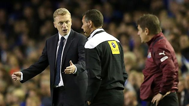 Everton manager David Moyes (left) speaks with fourth official Andre Marriner (centre) as Newcastle United assistant manager John Carver (right) looks on
