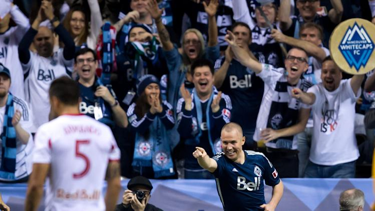 Vancouver Whitecaps' Kenny Miller, right, of Scotland, celebrates after scoring his second goal as New York Red Bulls' Armando, of Spain, looks on during second half MLS soccer action in Vancouver, B.C., on Saturday, March 8, 2014
