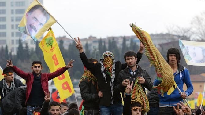 """In this photo taken Sunday, March 17, 2013, Kurds wave banners depicting imprisoned Kurdish rebel leader Abdullah Ocalan in Istanbul, Turkey. Imprisoned Kurdish rebel leader Abdullah Ocalan, in a message relayed by Kurdish legislators who visited him on his prison island, said Monday, March 18 that peace talks with Turkey are making """"positive progress"""" and that he plans to make a """"historic"""" announcement to coincide with a Kurdish spring festival. (AP Photo)"""
