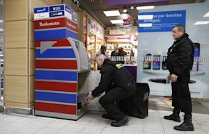 Bank staff fill a cash machine with euro currency in…
