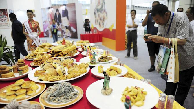 Visitor takes pictures at different types of food made of potatoes on display during the World Potato Congress on the outskirts of Beijing