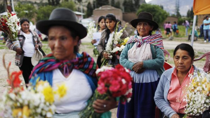 In this Nov. 26, 2015 photo, relatives of  34 people slain in 1992 by Shining Path guerrillas, gather before departing with the coffins of their loved ones to the cemetery for a mass burial service, in Valle Esmeralda de Huayao, Peru. People sang a local anthem that speaks of the hardships of life in this rural town of 1,200 people, where 87 percent are poor, 33 percent illiterate and most young people lack jobs and depend on subsistence corn farming. (AP Photo/Rodrigo Abd)