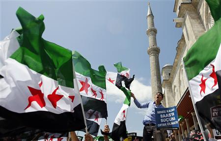 Demonstrators shout Islamic slogans as they wave Syrian opposition flags during a protest against Syria's President al-Assad at the courtyard of Fatih mosque in Istanbul