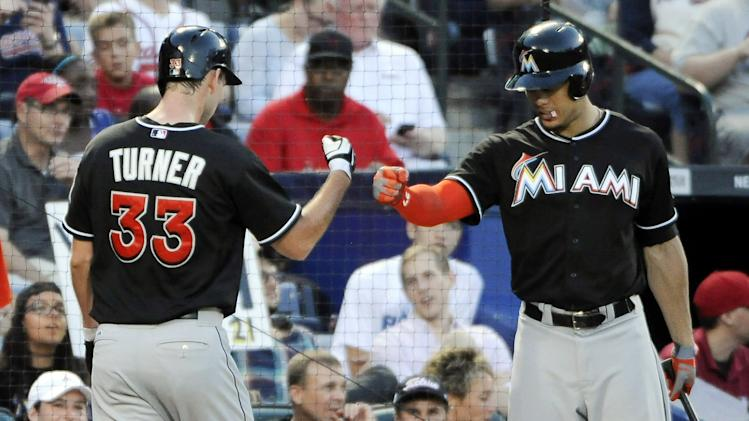 Miami Marlins pitcher Jacob Turner (33) and Donovan Solano fist bump after Turner scores against the Atlanta Braves during the fourth inning of a baseball game Tuesday, July 22, 2014, in Atlanta. (AP Photo/David Tulis)