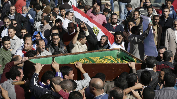 "Muslim Brotherhood and Egyptian President Morsi supporters carry a body one of six victims who were killed during Wednesday's clashes during their funeral outside Al Azhar mosque, the highest Islamic Sunni institution, Friday, Dec. 7, 2012. During the funeral, thousands Islamist mourners chanted, ""with blood and soul, we redeem Islam,"" pumping their fists in the air. ""Egypt is Islamic, it will not be secular, it will not be liberal,"" they chanted as they walked in a funeral procession that filled streets around Al-Azhar mosque. Thousands of Egyptians took to the streets after Friday midday prayers in rival rallies and marches across Cairo, as the standoff deepened over what opponents call the Islamist president's power grab, raising the specter of more violence.(AP Photo/Hassan Ammar)"