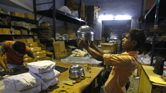 In this, June 2, 2012 photograph, a worker inspects a helmet before packing it for a Hollywood period movie at a workshop owned by Indian businessman Ashok Rai, unseen, in Sahibabad, India. From Hollywood war movies to Japanese Samurai films to battle re-enactments across Europe, Rai is one of the world's go-to men for historic weapons and battle attire. (AP Photo/Saurabh Das)