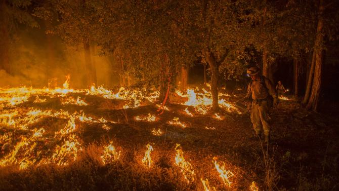 A firefighter lights a backfire to prevent the King Fire from spreading in Fresh Pond, California