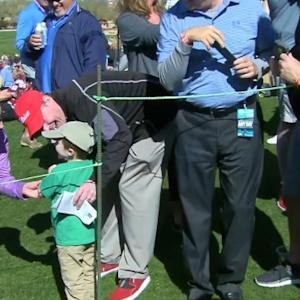 Bubba Watson gives his golf ball to a young fan at Waste Management