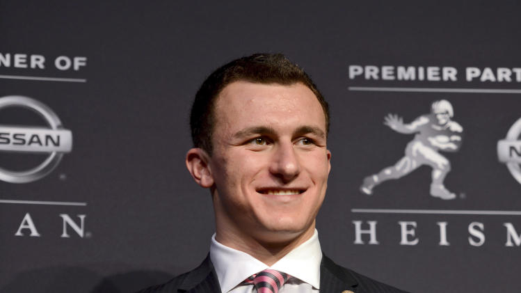 Heisman Trophy finalist Johnny Manziel of Texas A&M, poses with the Heisman Trophy following a news conference prior to the announcement of the winner, Saturday, Dec. 8, 2012 in New York. (AP Photo/Henny Ray Abrams)