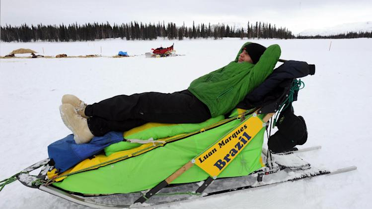 Luan Marques, of Brazil, rests on his sled while his dog team sleeps at the Finger Lake checkpoint in Alaska during the Iditarod Trail Sled Dog Race on Monday, March 4, 2013. (AP Photo/The Anchorage Daily News, Bill Roth)
