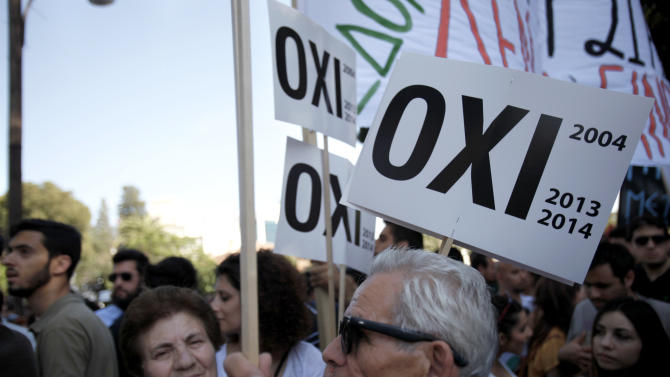"Protester hold banners that reading in Greek ""NO"" as they take part in an anti-bailout protest outside of the Cyprus' parliament in capital Nicosia, Tuesday, April 30, 2013. Cyprus' lawmakers are voting Tuesday on a multi-billion bailout agreement aimed at preventing the country from going bankrupt. The 56-seat parliament is expected to narrowly approve the 23 billion-euro ($30 billion) deal that the country struck with its euro partners and the International Monetary Fund last month. (AP Photo/Petros Karadjias)"