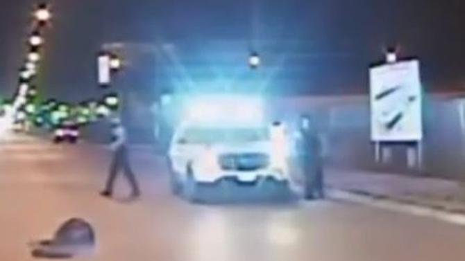 In this screen grab from a video released by the Chicago Police on November 24, 2015, officers walk past Laquan McDonald after he was shot by police in Chicago, Illinois on October 24, 2014