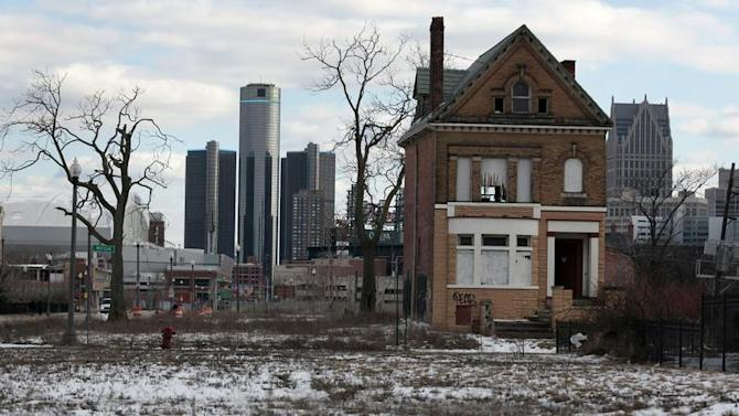 A vacant, boarded up house is seen in the once thriving Brush Park neighborhood with the downtown Detroit skyline behind it in Detroit,
