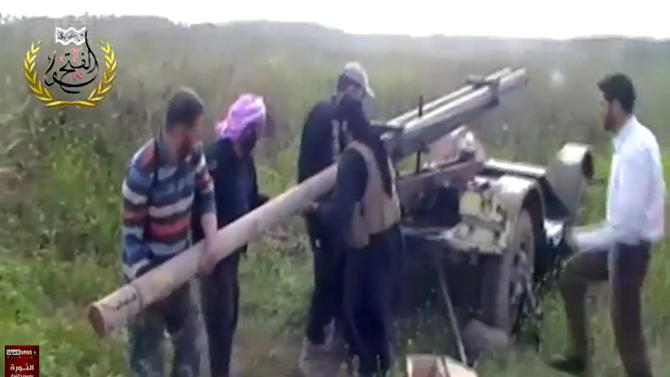 In this image taken from video obtained from Ugarit News, which has been authenticated based on its contents and other AP reporting, Syrian rebels prepare to launch a rocket at Mannagh air base  in Aleppo province, Syria, Monday, May 13, 2013. The Syrian government wants more details before deciding whether to take part in a proposed U.S.-Russian initiative to negotiate a peaceful end to Syria's crisis, the country's information minister said, staking out a similar position to the main opposition group.(AP Photo/Ugarit News via AP video)