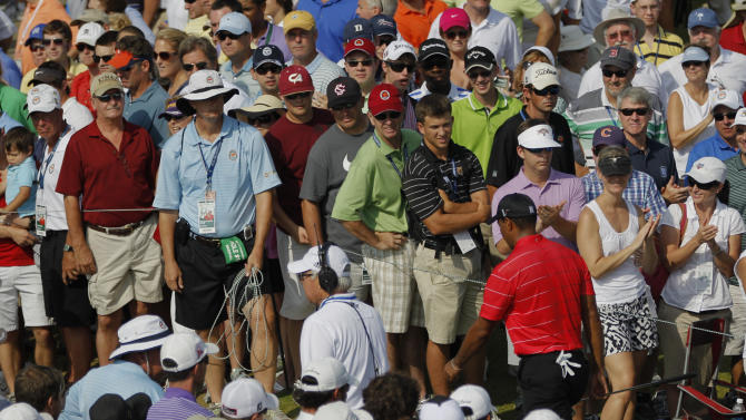 Tiger Woods walks through the gallery on his way to the 18th hole during the weather delayed third round of the PGA Championship golf tournament on the Ocean Course of the Kiawah Island Golf Resort in Kiawah Island, S.C., Sunday, Aug. 12, 2012. (AP Photo/Evan Vucci)