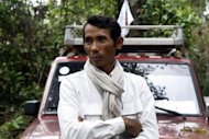 This handout photo taken in 2011 and released by the Cambodian Center for Human Rights shows Chhut Vuthy, president of the Natural Resource Conservation Group, standing in front of his car in Cambodia. The prominent Cambodian activist was fatally shot in a remote forest Thursday while documenting illegal logging in a clash that also killed a military police officer, authorities said