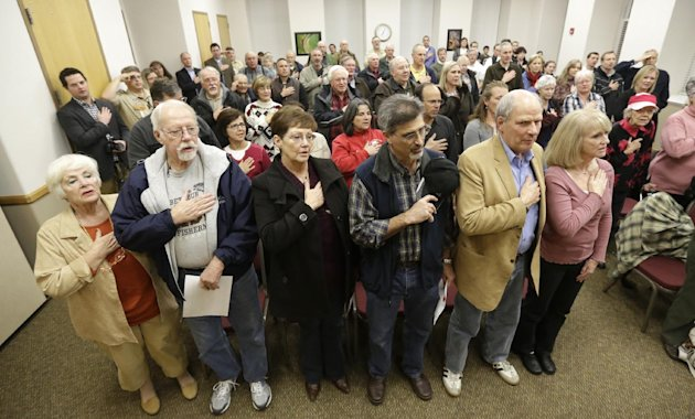 In this Feb. 7, 2013 photo, a group of supporters of Rep. Jason Chaffetz hold their hands over their hearts during the flag salute at a town hall meeting in Heber City, Utah. Chaffetz flew home from W