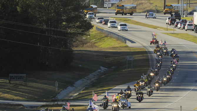 """The funeral procession of slain bus driver Charles """"Chuck"""" Poland makes its way down Highway 231 in Ozark, Ala., Sunday Over 60 motorcycles and dozens of school buses join the funeral procession. The Ozark Civic Center was packed with mourners for the funeral. Burial for Poland is in Newton, Ala. (AP Photo/AL.com, Joe Songer)"""