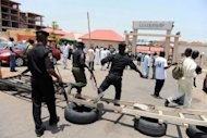 Policemen jump over a barricade at the premises of Leadership Newspaper following a rumour of impending attack in Abuja