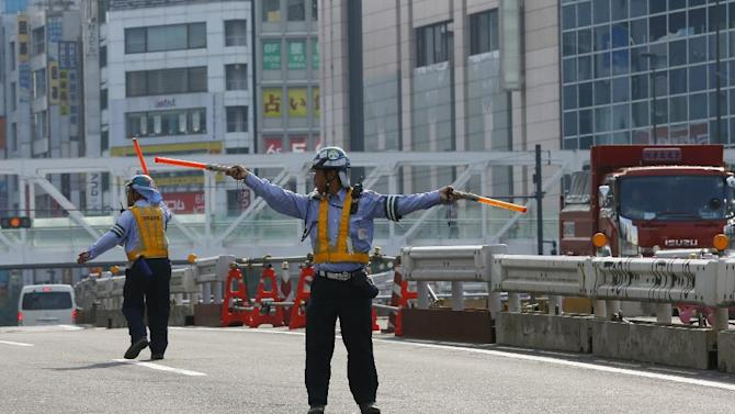 Guards control traffic in the middle of the street in front of the construction site in Tokyo Tuesday, July 28, 2015 as the temperature rises to 33 degrees Celsius (91.4 Fahrenheit). (AP Photo/Shizuo Kambayashi)