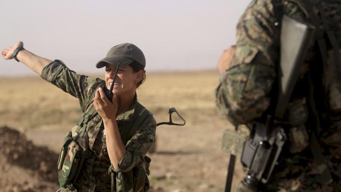 A female fighter of the Kurdish People's Protection Units gestures while using a walkie-talkie, in Qamishli